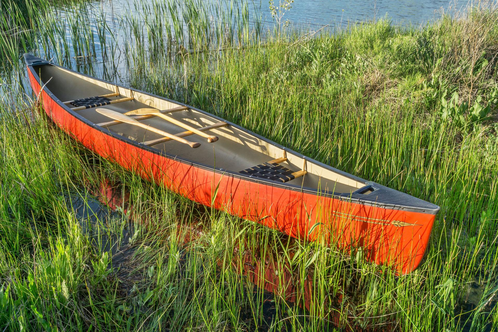 Ein rotes Ruderboot liegt am Ufer